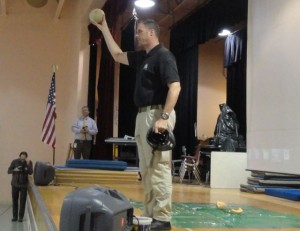 Sgt. Brian Hopely holds up a honeydew melon that survived a fall from overhead with the help of a bicycle helmet.