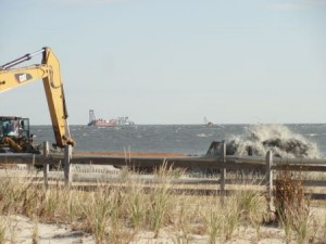 The dredge Illinois (background) is vacuuming sand from a borrow area off Surf Road and pumping it through an underwater pipeline to the beach in Ocean City, NJ.
