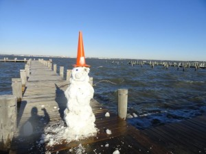 A snowman stands guard over the flooded public pier at Second Street and the bay on Sunday.