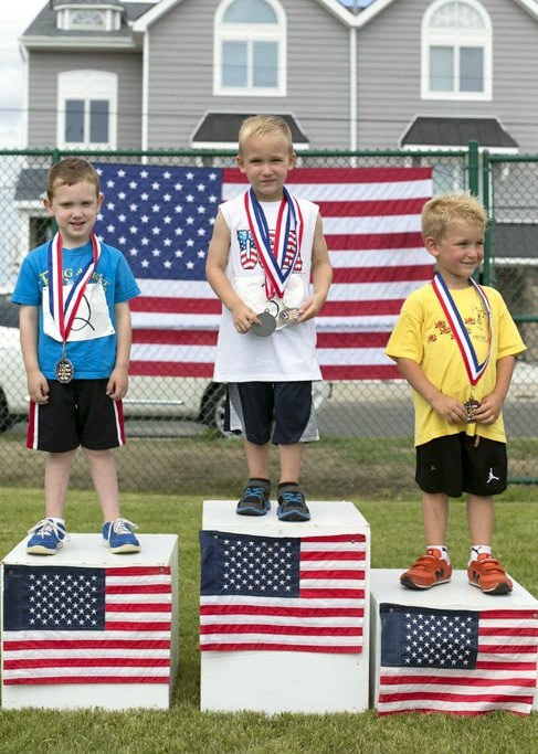 Winners will receive Olympic-style medals while standing on a three-tiered victory platform during Sea Isle City's annual Junior Olympics competition on July 4. Shown are past winners of the event's three-year old boy throwing competition: Ricky Marinari, of Coatesville, PA (center); Johnny Gillin, of Springfield, PA (left); and Max Delvescoro, of Lincoln University, PA.