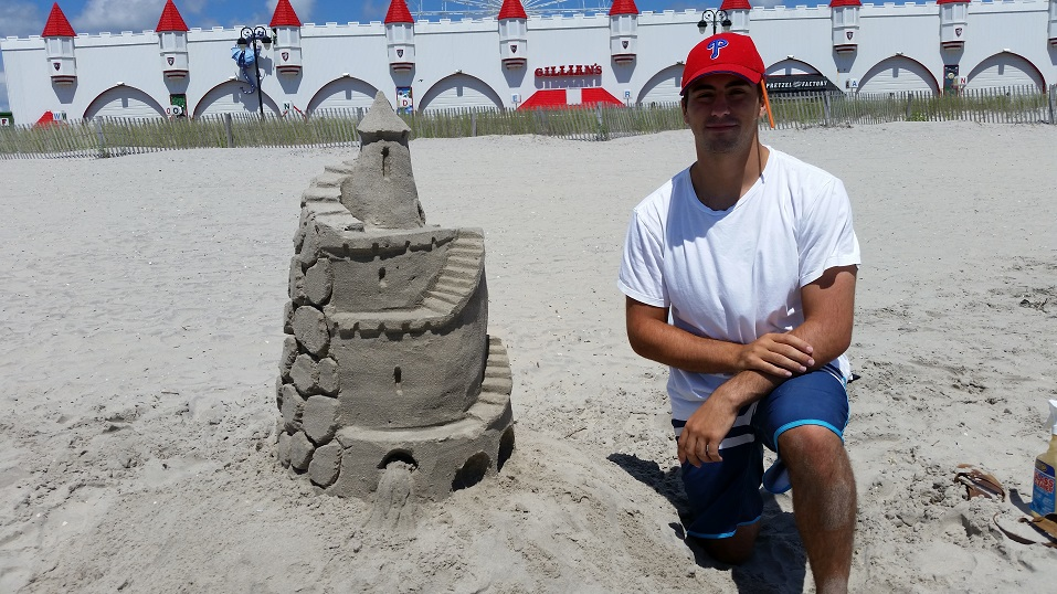 Frank Siderio, of West Chester, Pa., winner of the sand sculpting contest, shows off his elaborately crafted medieval castle.