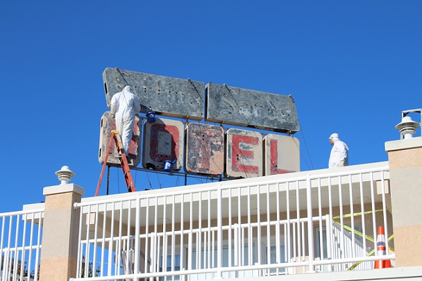 Workers sandblast the iconic neon sign of the Sifting Sands Motel on 9th St.