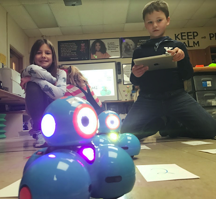 3rd grade student, Isabelle Tolbert, creating an algorithm for her robot to move towards the higher points on the board. The customized game board is projected onto the floor using a smart projector. As the robot moves and stops in the numbered squares the points disappear from the board.