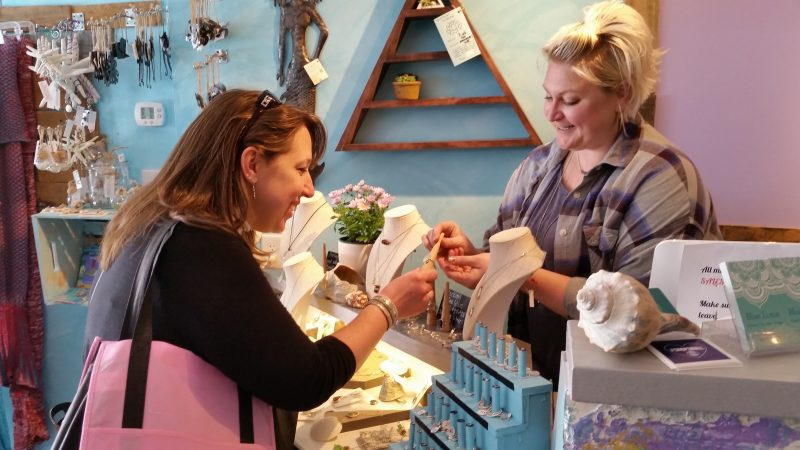 Lauren Waltz, right, owner of Blue Lotus, shows shopper Lori Gilliam some jewelry.